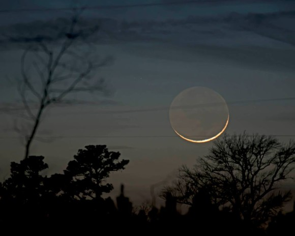 A very slim crescent moon, with earthshine.