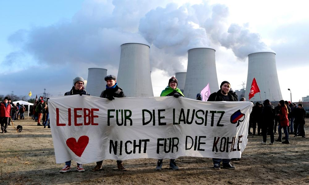 """Climate activists from Fridays for Future and Ende Gelaende protest at the Jänschwalde power station in Lusatia in 2019. The banner reads: """"Love for the Lausitz. Not for the coal."""""""