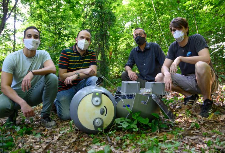 Four men in masks and casual garb squatting next to robot on the ground. Robot has sloth-like face.