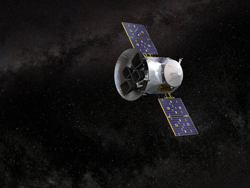 Cylindrical satellite with wide, flat solar panel on each side in space with stars in background.