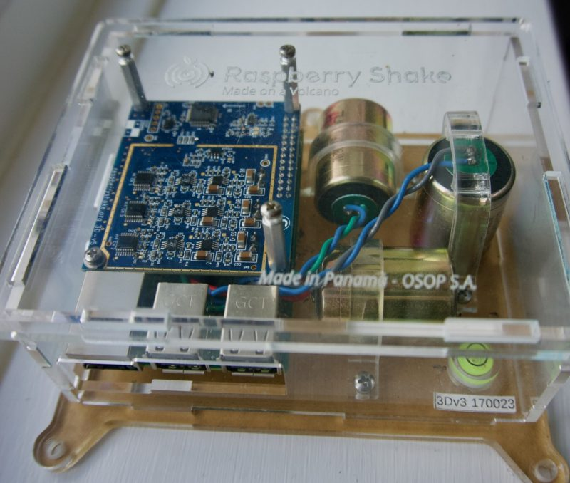 Clear plastic box containing electronics and two cylinders at right angles.