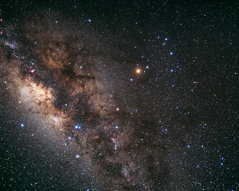 An image of the stars in Scorpius, with the Milky Way Galaxy in the background. The Milky Way appears diffuse and nebulous, mostly whitish-red with networks of dark dust lanes. Antares, the brightest star in Scorpius is prominent, shining with a reddish hue.