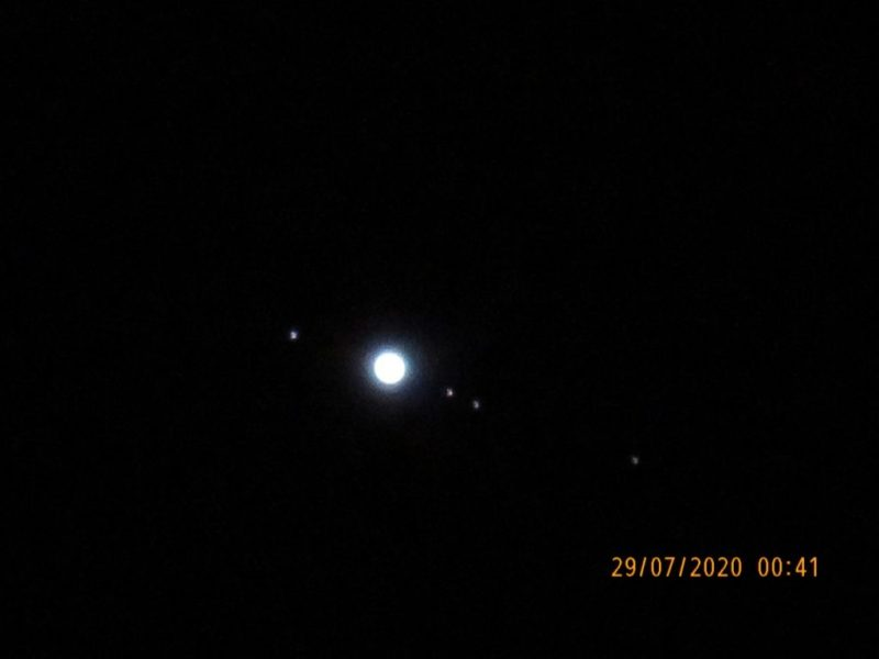 A disk, Jupiter, with 4 dots, the moons, 1 on left, 3 on right, in line with Jupiter's equator.