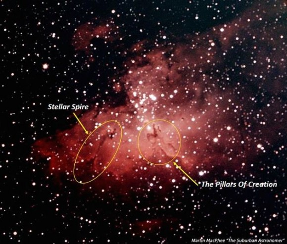 Reddish nebula in star field and with oval lines around two dark features.