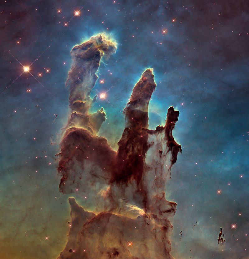 Towering plumes of gas and dust with stars in background.