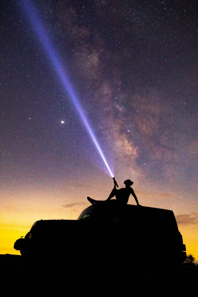Silhouette of a woman sitting atop a car, shining a flashlight at the sky, with the Milky Way in the background.