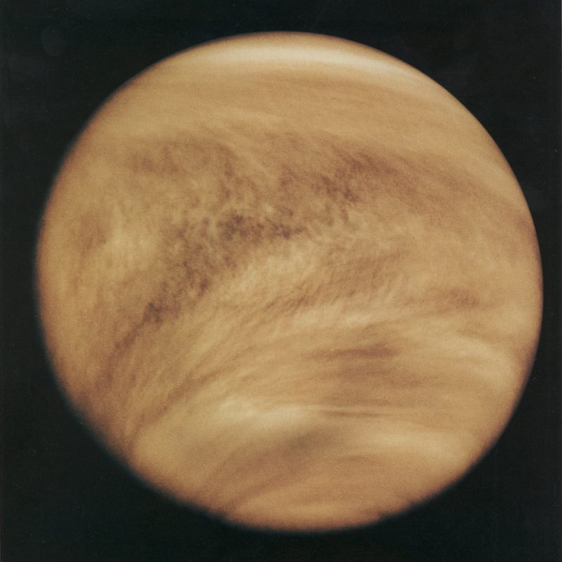 Brownish-colored clouds covering a planet, on black background.