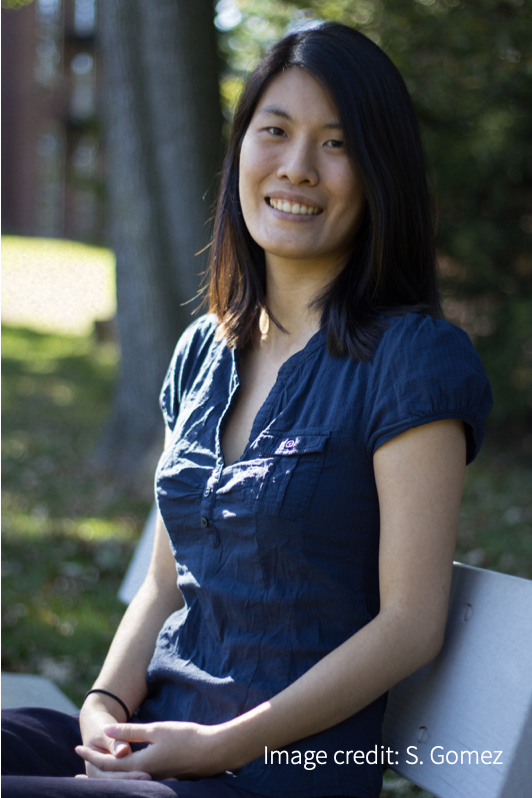 Smiling woman in blue blouse, sitting on bench with tree in background.