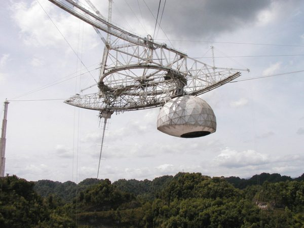 Geodesic dome hanging from trusses above Arecibo telescope dish.