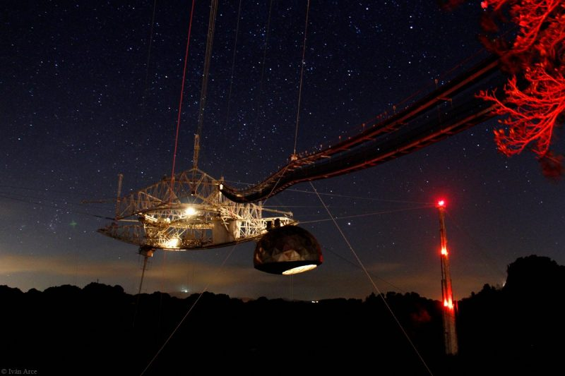 Night view of brightly lit truss construction high above telescope dish.