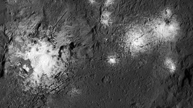 Large and small bright white patches on a gray cratered surface.