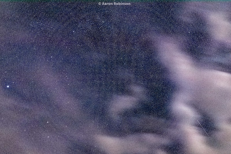 Blurry clouds in a sky with very many stars and a white streak on the lower right.