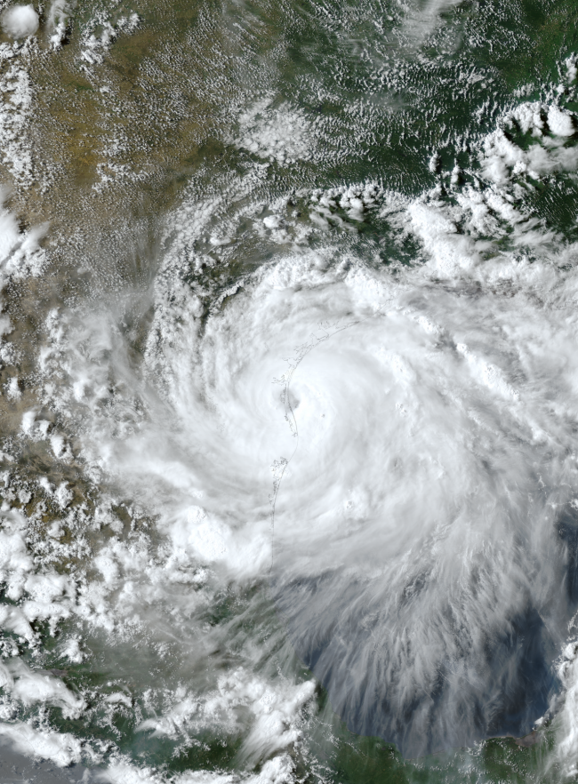Orbital view of huge white spiral with dark dot in the middle next to Texas coastline.
