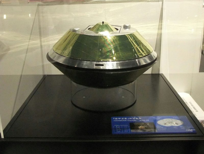 A 'flying saucer' shaped capsule, inside a glass display case.