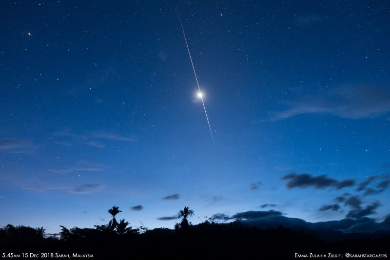 Bright light and elongated flash in dark blue sky with small clouds and stars.