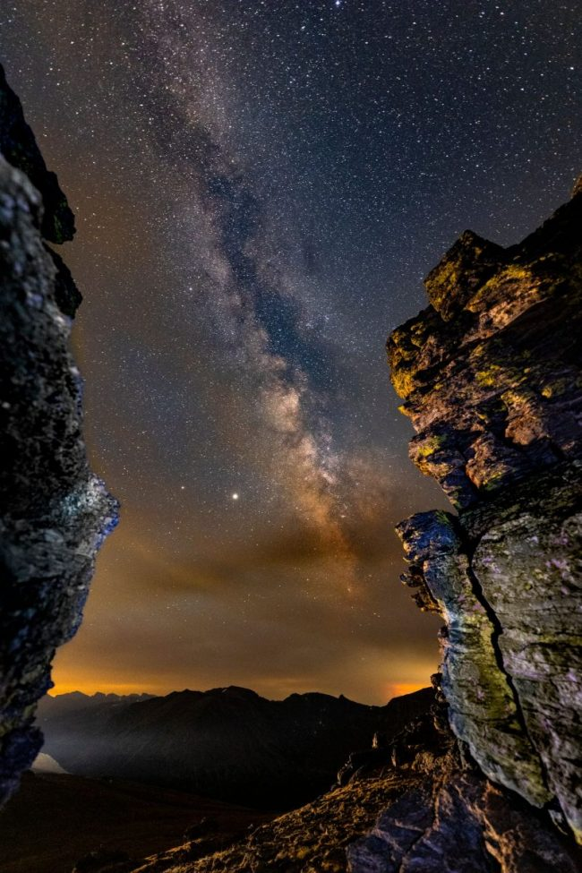 Edgewise view of the summer Milky Way, between two rock cliffs, with red clouds in the distance.