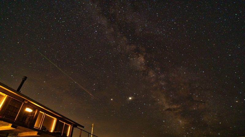 Edgewise view of the summer Milky Way, on a dark night, with a long, thin streak next to it.