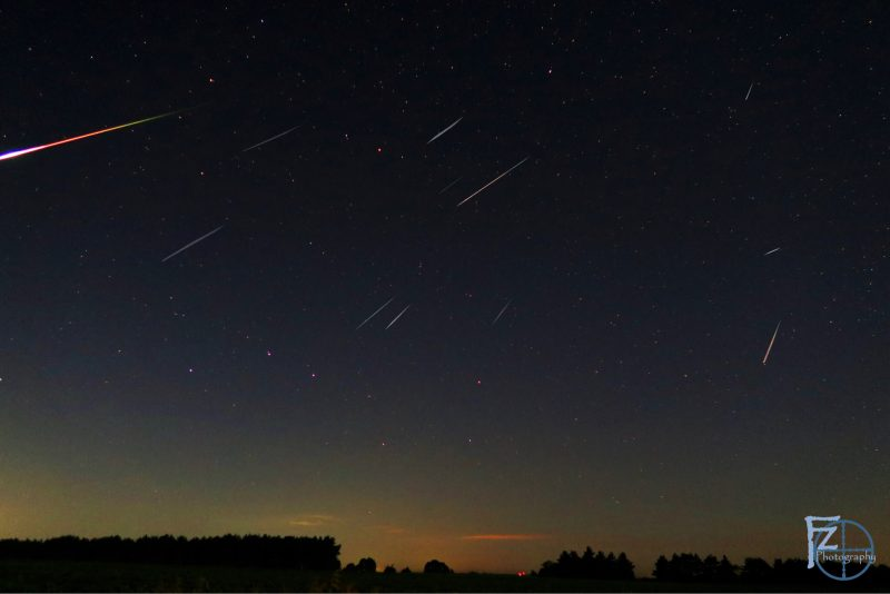 Dark horizon and night sky with multiple bright streaks diagonally right to left.