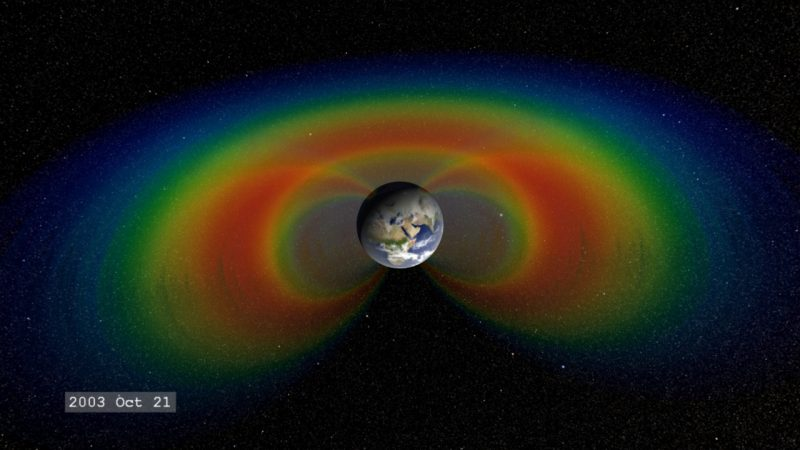 Earth with fuzzy false-color donuts around it cut away to show their depth.