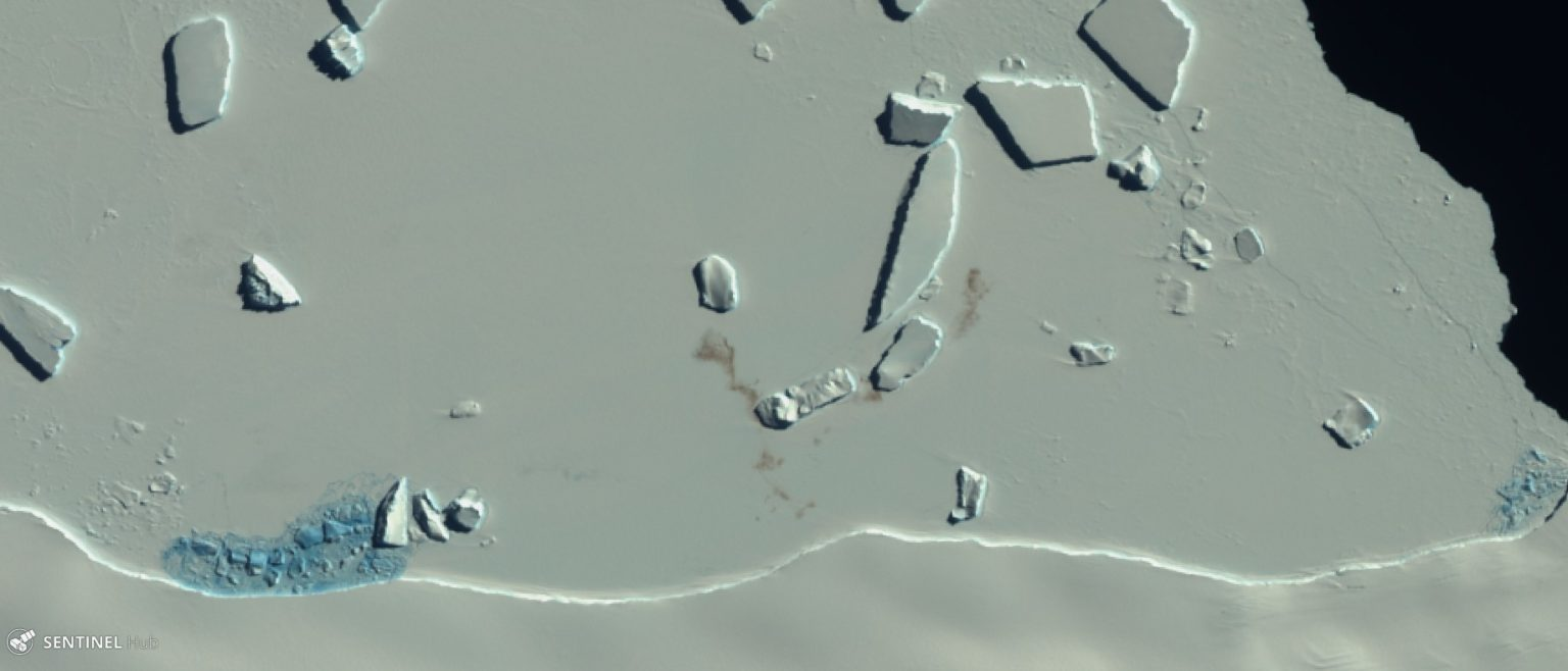 Orbital view of vast area of ice, next to deep blue sea, with small reddish smudges on the ice.