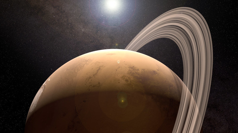 Reddish planet with rings, and sun and stars in background.