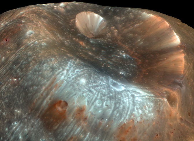 Very large crater on blue and pink landscape with many small craters.