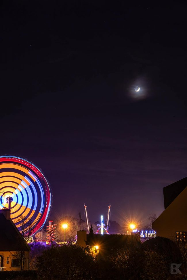 Night scene with large ferris wheel, with a crescent moon above it.