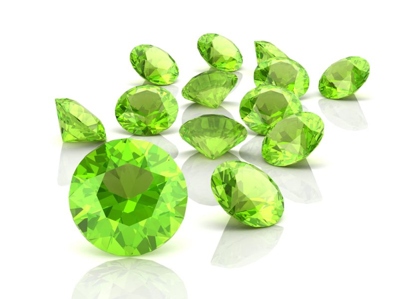 About a dozen loose faceted lime-green jewels.
