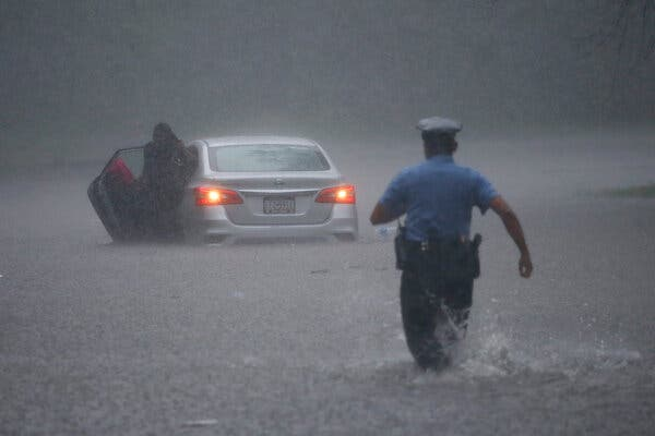 A Philadelphia police officer and a stranded motorist on Tuesday during Tropical Storm Isaias.