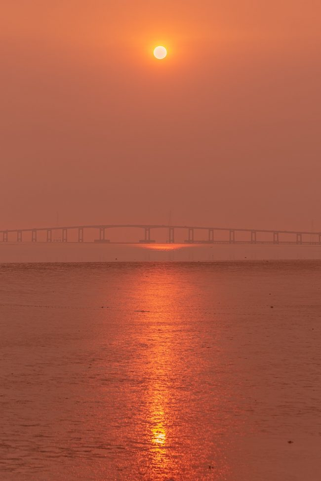 Smoky sunrise over a body of water, with a bridge in the distance.