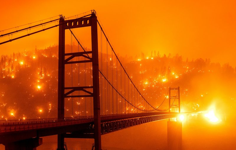 A bridge in the foreground, orange skies, fires burning all over hills in the distance.