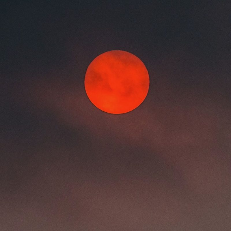 Very red full moon, amidst clouds.