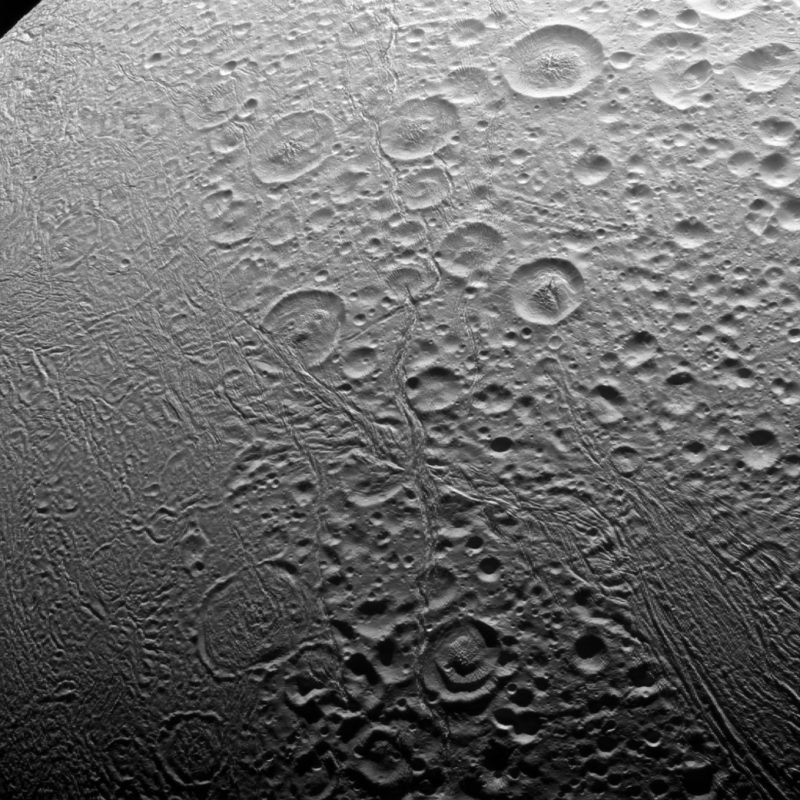 Grayish moon covered in craters and some stripes or cracks.