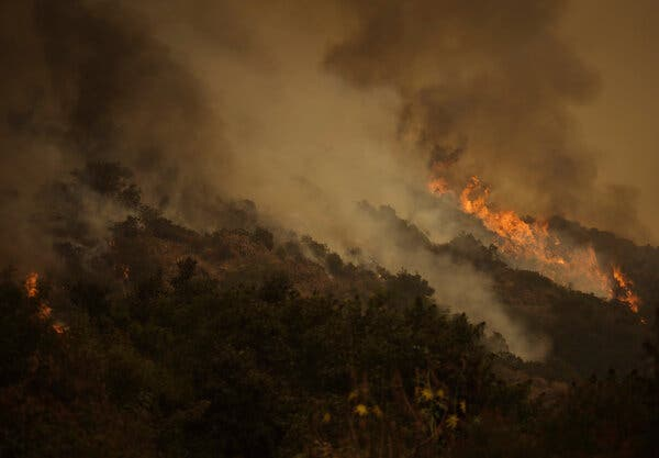 Firefighters battling the Bobcat Fire in Santa Anita Canyon near Los Angeles on Sunday. Fires have burned millions of acres across the West and shrouded the region in smoke.