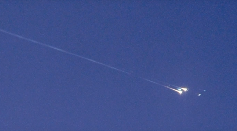 A fiery meteor flashing across a daylight sky with parts seeming to explode off.