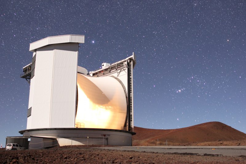 Large telescope with hills and starry sky behind it.