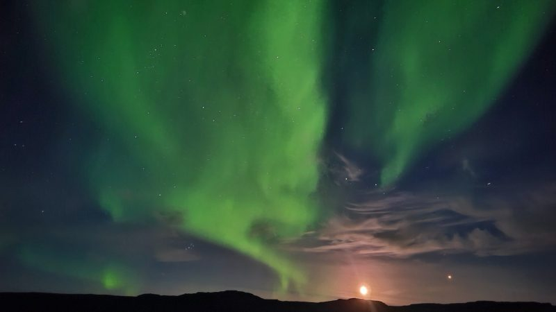Moon and Mars rising above a ridgeline, with a glorious display of green northern lights filling most of the sky.