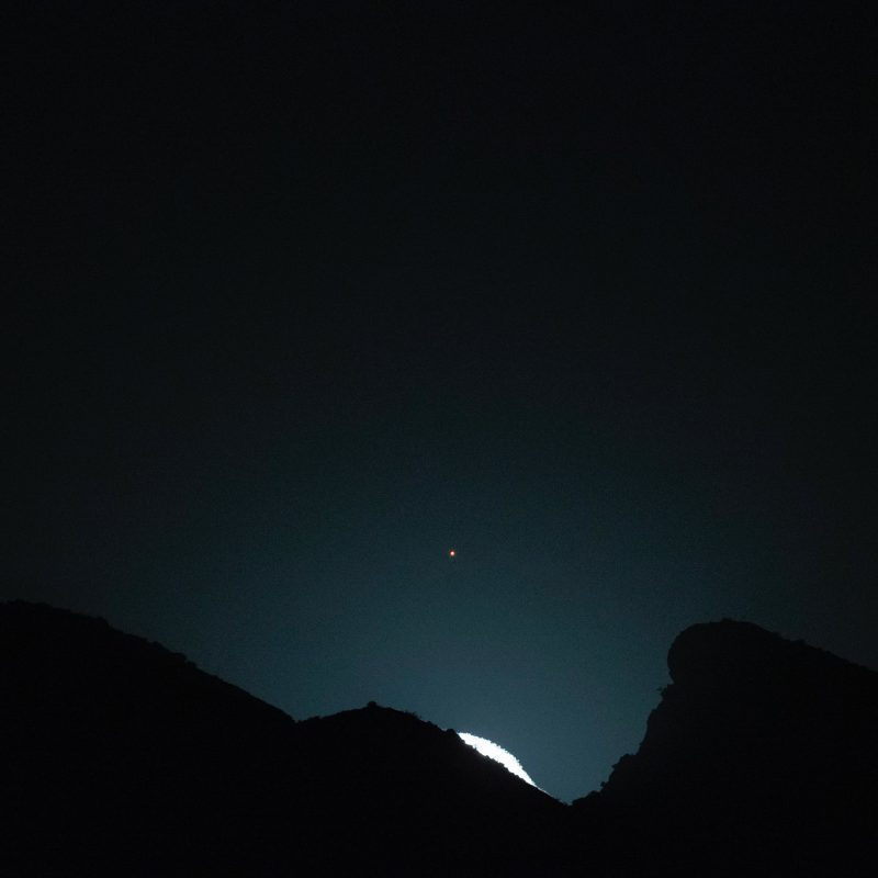 The edge of the bright moon appearing above a ridgeline, with reddish dot of Mars above.