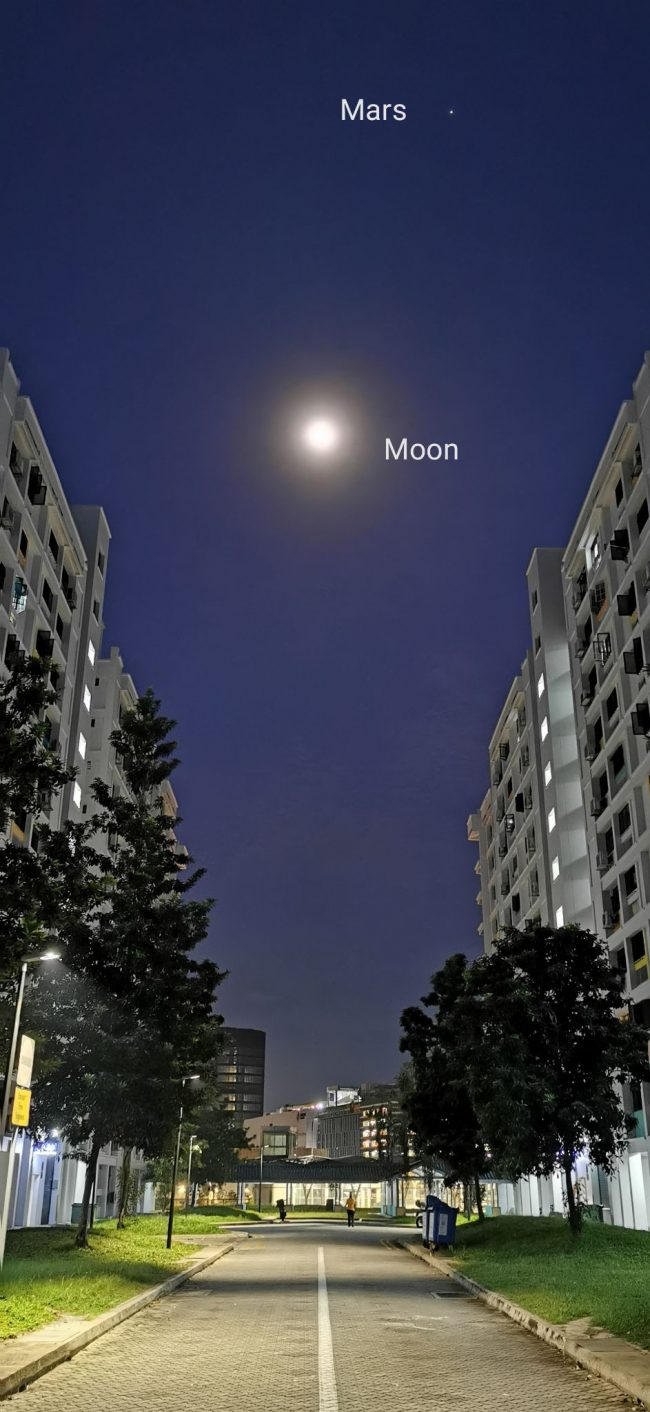 The glowing moon and Mars above tall buildings along a street in Singapore.