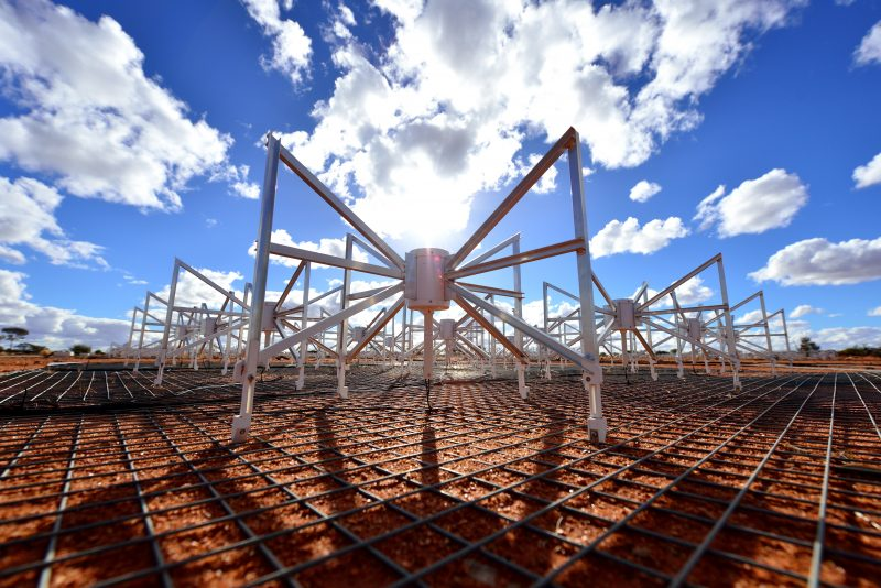 Spider-like standing structures in field with blue sky and puffy clouds overhead.
