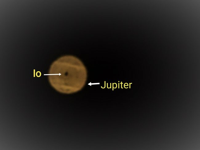 Fuzzy, banded Jupiter, with Io's dark dot-like shadow in the middle, with labels.