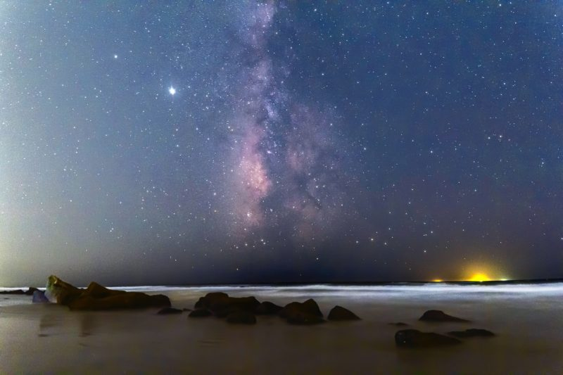 Edgewise view of the summer Milky Way, soaring straight up from the horizon, on a dark night.