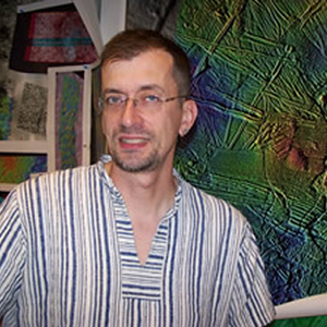 Smiling man in eyeglasses and striped shirt.