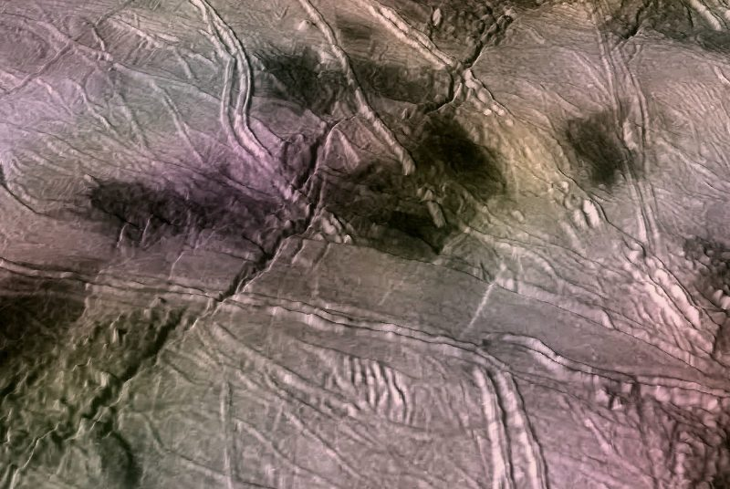 Rough surface covered with cracks and dark blotches.