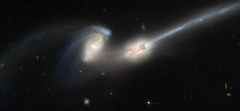 Two galaxies close together stretched irregularly with long streamers of stars.