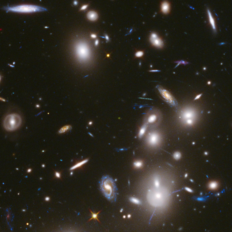 A cluster of galaxies - lots of bright oblongs and spirals, different sizes, all angles, on a black background.