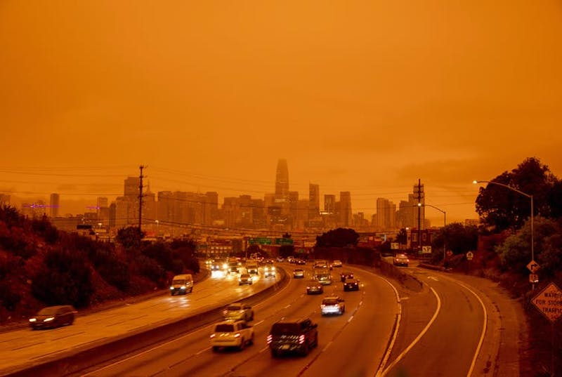 Freeway curving into a large city, the sky and air orange and headlights on.
