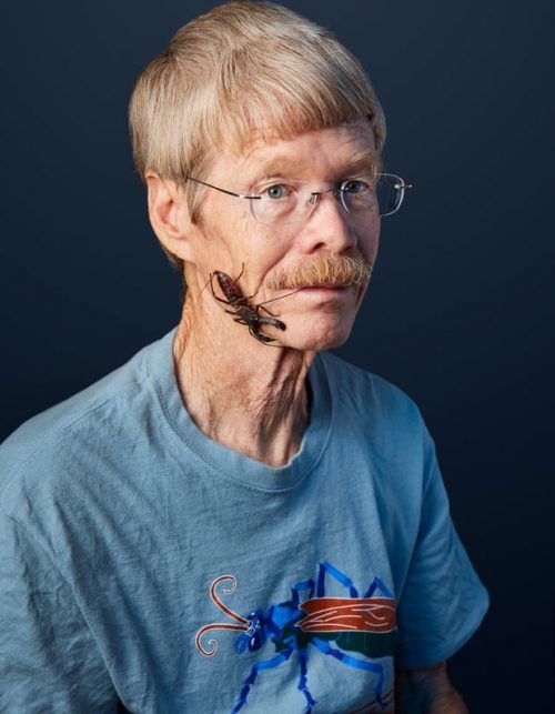 Oldish blond man with a mustache and a 2-inch insect with large mandibles clinging to his face.