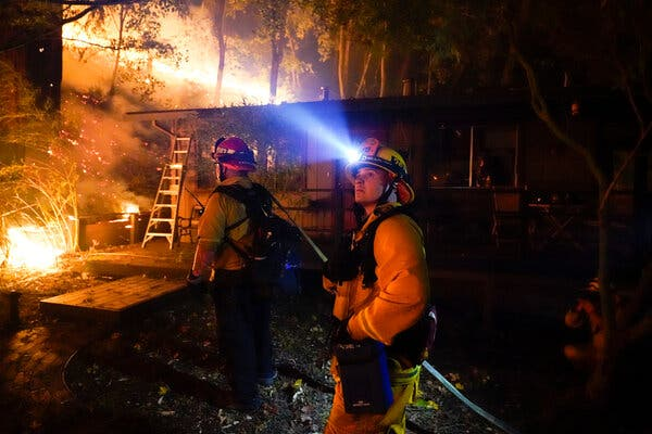 Firefighters in Boulder Creek, Calif., last month. Many firefighters themselves live in fire-prone areas and are affected by the insurance crisis.