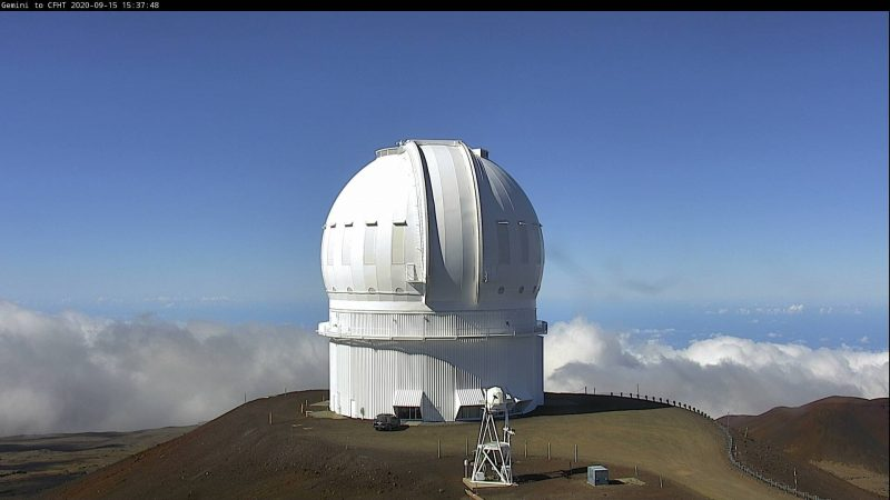 White telescope dome on top of mountain with clouds and blue sky in background.